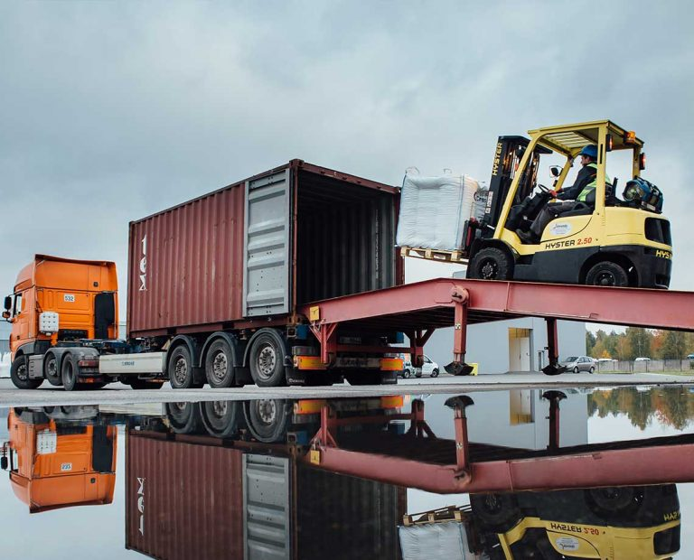 Forklift loading CrossChem products into a container.